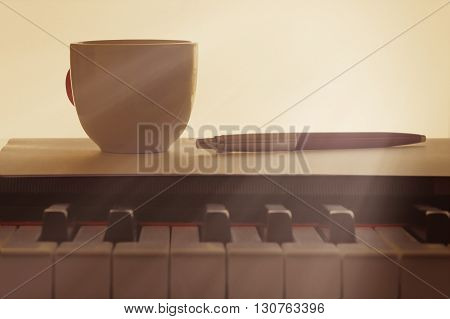 Cup of coffee on an old piano keyboard while composing. Evening time and some sun rays. Empty copy space for editor's text.