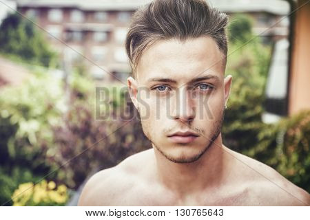 Headshot of handsome shirtless young man outdoor, looking at camera