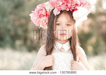 Beautiful baby girl 4-5 year old wearing peony wreath outdoors. Looking at camera. Childhood. Summer season.