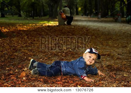 Baby plays in fallen leaves.