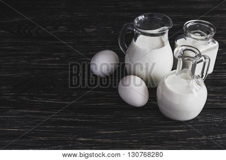 Milk Jars And Eggs On Wooden Background