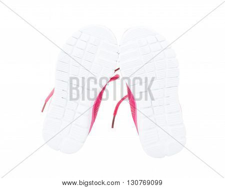 Pair of pink training shoes for girls. Shoe sole side. Isolated on a white background.