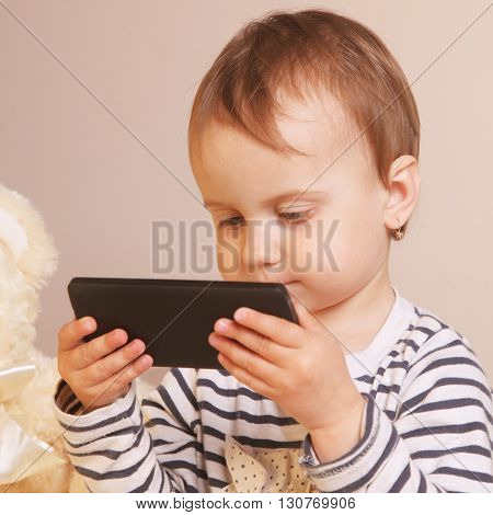 Little beautiful girl with smart phone (close up)