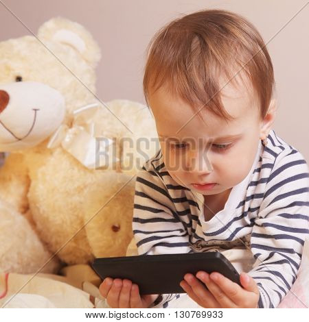 Little beautiful girl with smart phone on the background of Bear toy