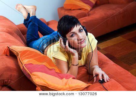Joven es escuchar música en un auricular en el salón.