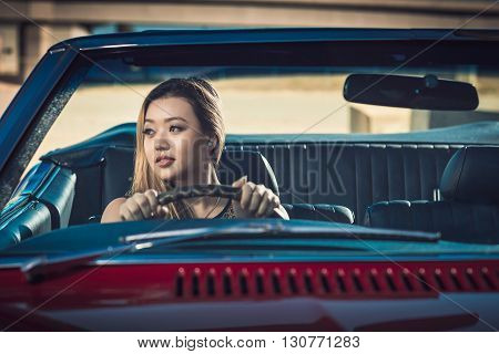 Smiling attractive girl sitting in vintage car South Australia