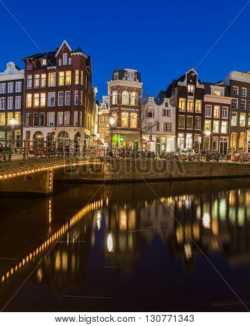 AMSTERDAM NETHERLANDS - 16TH FEBRUARY 2016: A view along the Keizersgracht canal in Amsterdam at night. Buildings bridges cars and bikes can be seen.