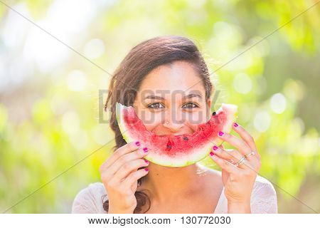 Beautiful young woman showing a slice of watermelon as a smile. She is caucasian she wear a white dress and she has a braid on the shoulder. Summer and lifestyle concepts.