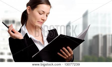 Young businesswoman reads from an open open folder and she is thinking.