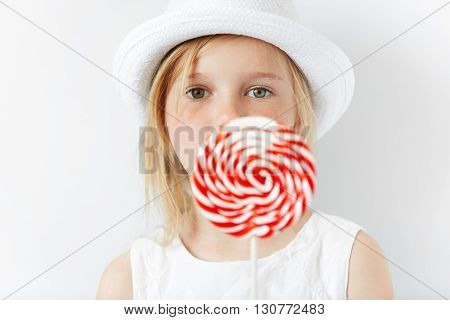Close Up Shot Of Beautiful Preschool Child In Stylish White Clothes, Enjoying Sweet Candy, Posing Ag