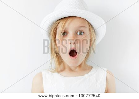 Portrait Of Emotional Beautiful Blonde Little Girl Wearing Trendy White Clothes. Adorable Surprised