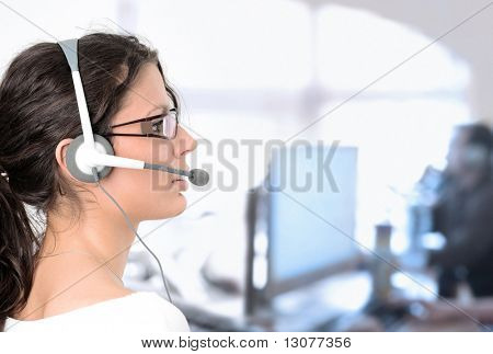 Young female customer service representative recieves calls on a headset while an IT specialist works on a computer in the background.