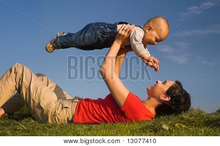Baby and his mother are having outdoor fun together and they are smiling a lot. There are nice afternoon lights.