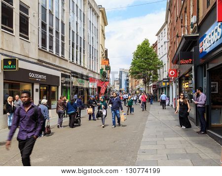 NOTTINGHAM ENGLAND - MAY 17: Various people walking by the shops on Nottingham's busy Clumber Street. Various major retail stores visible. In Nottingham England. On 17th May 2016.