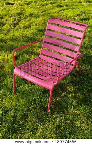 Pink metal relax chair on the green grass in garden
