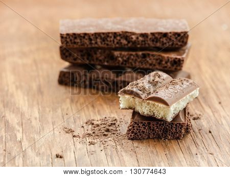 part porous chocolate close-up on a wooden background