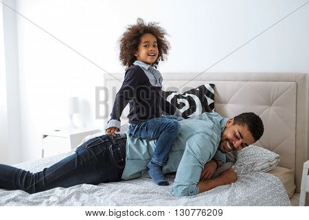Cute little kid playing with daddy at home.
