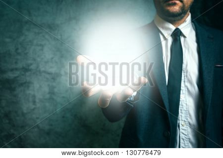 Business vison concept with elegant adult businessman holding bright light of new ideas in hand