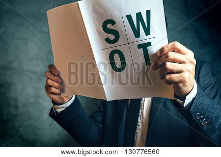 Businessman reading SWOT analysis report documentation male businessperson in office