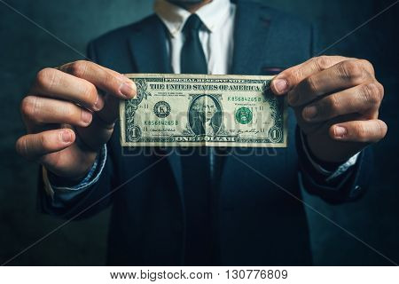 Businessman holding one USA dollar bill in his hands