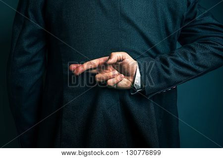 Dishonest businessman telling lies lying businessperson holding fingers crossed behind his back