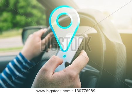 Female driving car and using gps navigation app on smartphone to find destination using mobile phone in traffic.