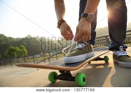 closeup of young skateboarder tying shoelace at skatepark