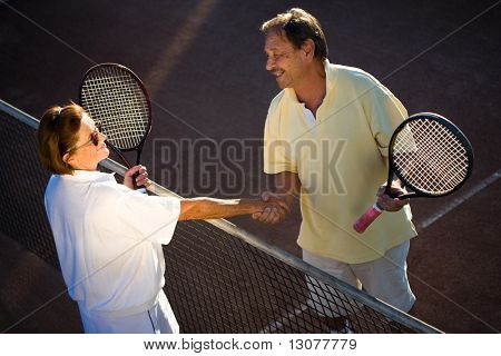 Active senior couple is shaking hands on the tennis court with tennis rackets in hand. Outdoor, sunlight.