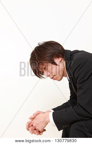 portrait of young Japanese businessman depressed on white background