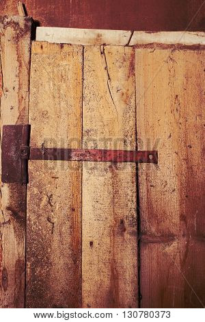 Wooden door with a metal hinge. Building feature