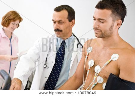 Medical team performing an EKG test on  young male patient. Real people, real location, not a staged photo with models. Focus is placed on the doctor.