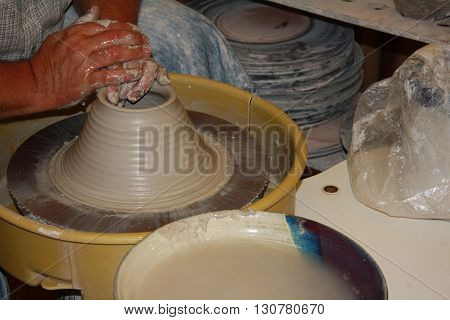 Potters wheel molding and shaping clay with hands.