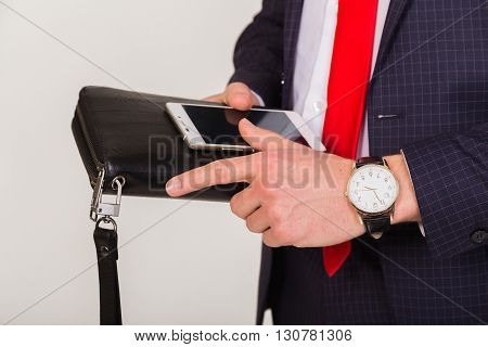 Phone close-up in human hands.Attributes of the success in the hands of the respectable man. Purse mobile phone and an expensive watch