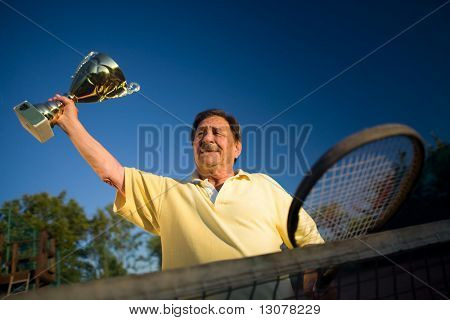 Active senior man in his 70s is posing on the tennis court with cups in hands. Outdoor, sunlight.