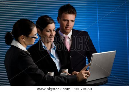Young business people working on laptop at late night. Selective focus is placed on the woman in the middle.