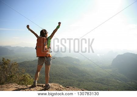 cheering woman hiker at sunrise mountain peak