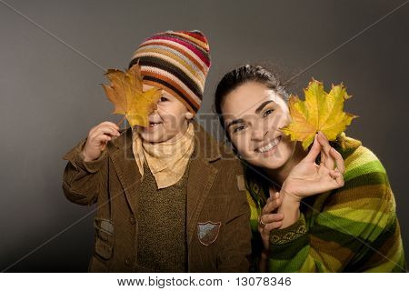 2 years old baby and mother playing with fallen autumn leaves.