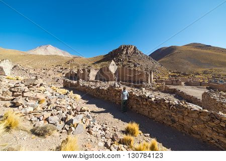 Tourist on the highlands of the Andes on the way to the famous Uyuni Salt Flat among the most important travel destination in Bolivia. Abandoned and ruined old colonial village.