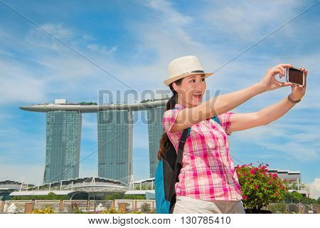 Smiling Young Woman Making Selfie Near Marina Bay Sands Hotel
