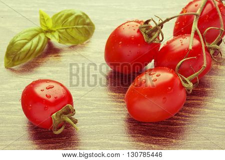 Cherry tomatoes on a dark table. A bunch in drops of water. Basil leaf. Retro effect.