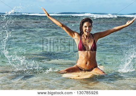 Attractive young female surfer floating upright on surfboard, splashing happily
