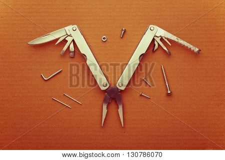 Multitool bird on cardboard. A tool for a variety of cases. Retro effect.