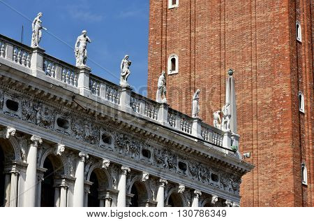 Beautiful balustrade with statues of the old St Mark Library designed by famous renaissance architect Sansovino in the 16th century and close to the belfry