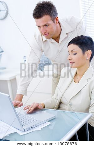 Businessman and businesswoman working on laptop computer at desk in brightly lit office.