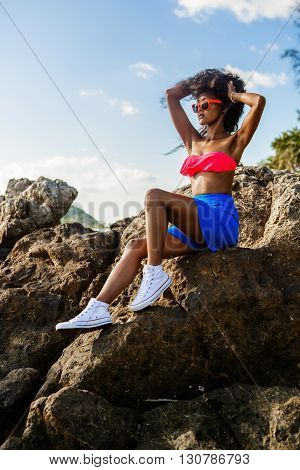 Beautiful Teenage Black Girl In Blue Skirt And Pink Bra On The Rock.