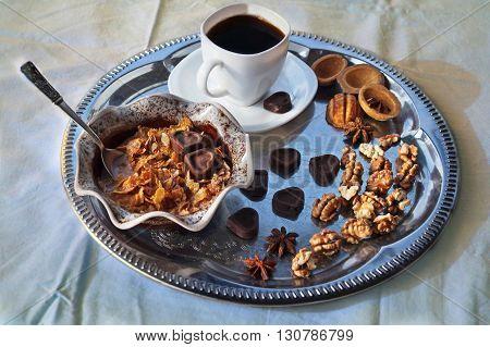 A Cup of coffee, chocolate, walnuts, milk, muesli, silver plate