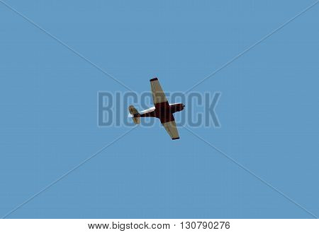 Small engine plane in the blue sky.