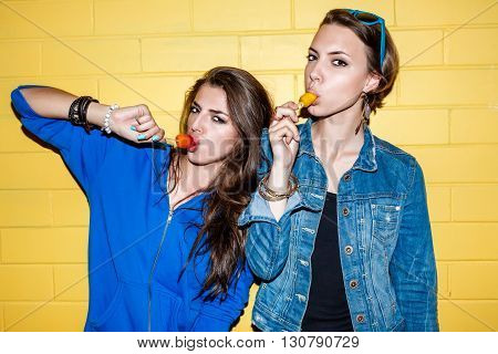 Lifestyle portrait of two beautiful best friends hipster girls wearing stylish bright outfits and having great time. Standing together near yellow brick wall enjoying day off have fun and eating sweet ice-cream.