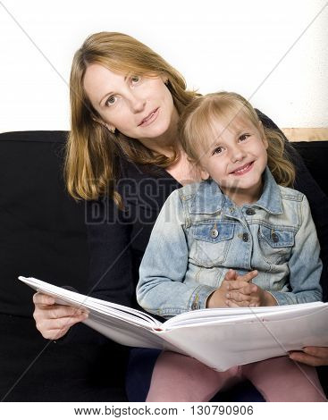 mature woman with granddaughter reading book at home, happy family together, lifestyle people concept