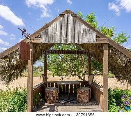 Wooden pergola with roof covered with palm branches, inside a table and two chairs